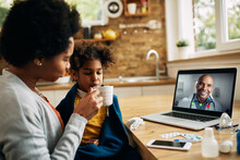Black Mother Giving Cup Of Tea To Sick Small Daughter While Having Video Call With Family Doctor From Home.