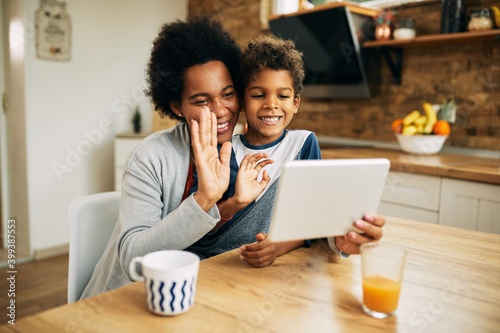 Canvastavla Happy African American mother and son waving during video call at home
