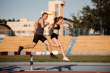 Sportswoman And Sportsman Leaping Over Barrier At Stadium