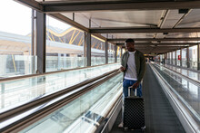 Young Man On The Walkway At The Airport With Mobile Phone