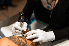 Crop Person Making Four Elements Tattoo On Arm Man