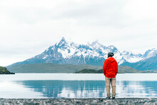 Unrecognizable Young Man Standing In Front Of A Lake And A Mountain