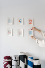 Crop Artist Hanging Small Paintings On White Wall In Studio