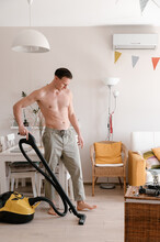 Shirtless Man Cleaning Floor At Home