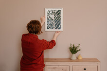 Woman Adjusting Frame With Mosaic On Wall