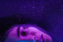 Half Of Woman Face Under Cosmic Glitter Water With Neon Lights Looking To Camera