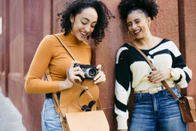 Girls Leaning Against Wall With Camera