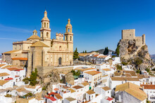Aerial View Of A Church And A Castle On Top Of A Hill With White Houses Surrounding Them Of The Town Of Olvera, Cadiz, Spain.