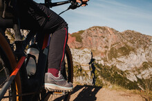 Woman On Mountain Bike Standing Against Mountain At Somiedo Natural Park, Spain