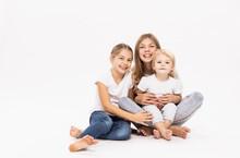 Female Toddler Sitting On Elder Sister's Lap Against White Background In Studio