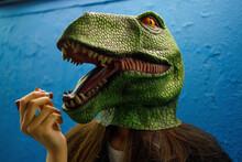 Female Applying Lipstick While Wearing Dinosaur Mask Against Blue Wall