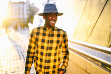 Smiling African Man In Yellow Plaid Shirt Standing In City During Sunset