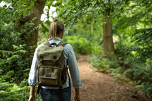 Senior Woman Walking With Backpack In Forest