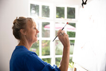 Active Senior Woman Painting Picture On Canvas While Standing At Home