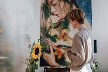 Mid Adult Female Artist Painting On Canvas In Studio