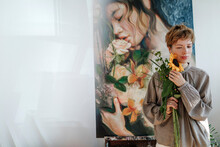 Thoughtful Mid Adult Female Artist Holding Sunflower While Standing Against Artwork In Studio