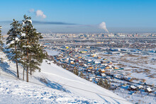 Russia, Republic Of Sakha, Yakutsk, Snowcapped Hill With City Houses In Background