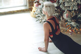 Portrait of gorgeous young woman practicing yoga indoors at Christmas time. Beautiful girl practice in the class. Calm and relax, woman happiness. High quality photo.
