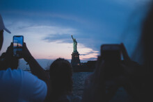 People Taking A Photo Of Statue Of Liberty At Sunset