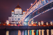 Festive Evening In Moscow. The Capital Of Russia Is Decorated For Christmas. New Year In Moscow. A Bridge With Garlands Leads To The Church Of The Savior. Illumination Near The Moscow River.