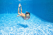 Child Swims Underwater In Swimming Pool, Little Active Girl Dives And Has Fun Under Water, Kid Fitness And Sport On Family Vacation