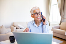 Smiling Mature Beautiful Business Woman With White Hair Working On Laptop In Bright Modern Home Office. Business Woman Talking On Her Mobile Phone While Working From Home