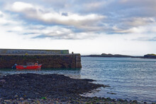 A Small Wooden Fishing Boat With A Reed Hull Moored Up Alongside The Traditional Old Stone Quay At Catterline, On The East Coast Of Scotland.