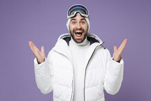 Surprised Skier Man In Warm Windbreaker Jacket Ski Goggles Mask Spreading Hands Going To Spend Extreme Weekend Winter Season In Mountains Isolated On Purple Background. People Lifestyle Hobby Concept.