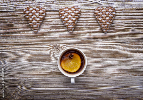 Stampa su Tela three fresh heart-shaped glazed gingerbread cookies and a cup of orange anise tea