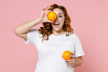 Excited Young Redhead Plus Size Body Positive Woman 20s Wearing White Casual T-shirt Covering Eye With Ripe Fresh Orange Fruits Looking Camera Isolated On Pastel Pink Color Background Studio Portrait.
