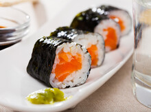 Delicious Makizushi Set With Salmon Served On White Plate With Piquant Wasabi Paste And Soy Sauce