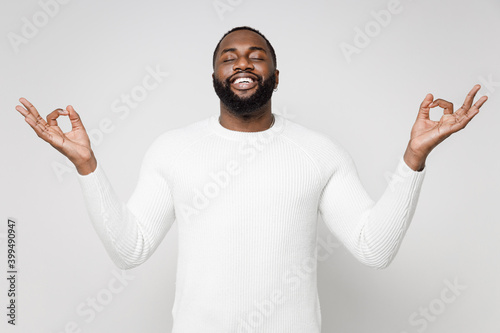 Obraz Smiling young african american man 20s wearing casual basic sweater standing hold hands in yoga gesture relaxing meditating trying to calm down isolated on white color wall background studio portrait. - fototapety do salonu