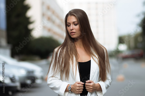 Fotografija Young confident woman in stylish white outfit in park