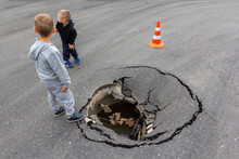 Children Play On Road Near Huge Deep Sinkhole In Asphalt Surface. Risk Of Injury To Child. Damaged Sink Hole On City Street