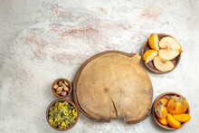 Far-off Shot Of Wooden Platter And Bowl Of Dry Lavender And Flower And Fruits On Marble Background