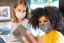 Two Young Students In The Library Take A Moment To Take A Picture Of Themselves To Post On Social Media, Prevention And Safety During The Epidemic With Facemask, Concept Of Cultural Integration