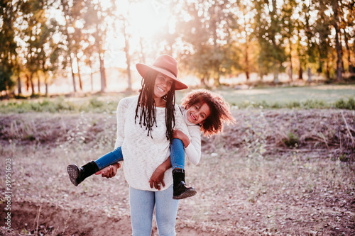 Obraz na plátně portrait of hispanic mother and afro kid girl playing outdoors at sunset during golden hour