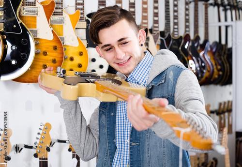 Fotografija Smiling russian teenage customer deciding on suitable amp in guitar shop