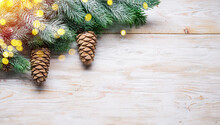 Snowy Fir Branch With Fir Cones On Wooden Table. Christmas Or New Year Holiday Background.