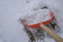 Red Shovel Cleaning Up The Snow On A Winter Day. Macro. Close-up. Winter Weather.
