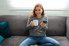 Happy Woman Relaxing On The Sofa With Her Smartphone And A Cup Of Tea