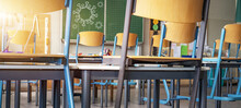 CORONAVIRUS - School Closed - Empty Classroom With High Chairs And Empty Green Blackboard / Chalkboard With Cartoon Virus Symbol