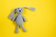Grey Knitted Toy Rabbit On Yellow Background With Copy Space. Top View