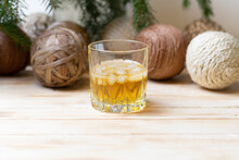 Glass Of Gold Rum With Ice On Wooden Table Witn Christmas Tree And Balls Decoration