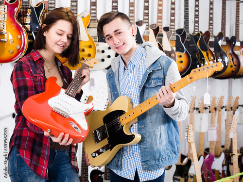 Slika na platnu Young female and male are deciding on suitable amp in guitar shop
