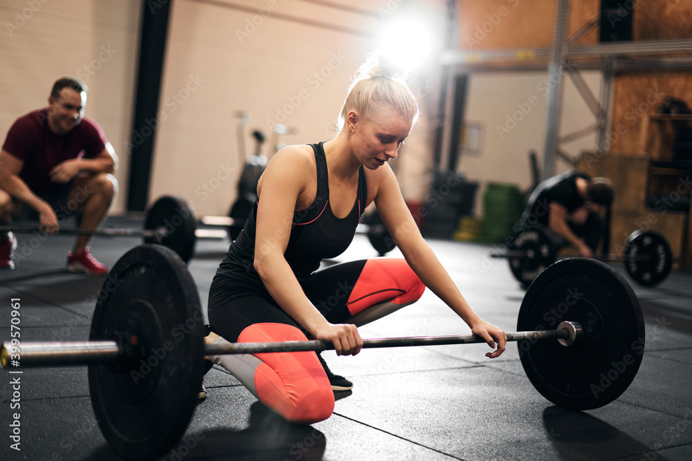 Fototapeta Fit young woman looking tired after a weightlifting class