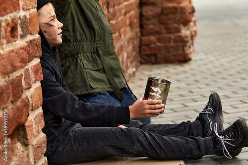 Fotografia dirty and little homeless boy is begging in the buzy street, child look to the crowd with sad face hoping for sympathy