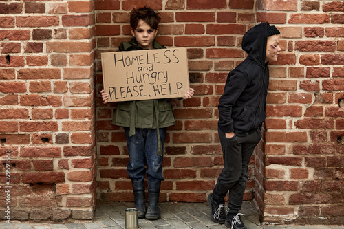 Tela poor little children begging in the buzy street in big city, boys look to the crowd with sad face hoping for sympathy