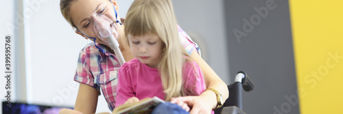 Foto Woman in wheelchair and with an oxygen mask on her face is reading book with little girl