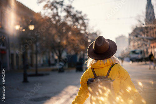 Leinwand Poster Young woman traveler in yellow jacket and hat walking in a european city on a su
